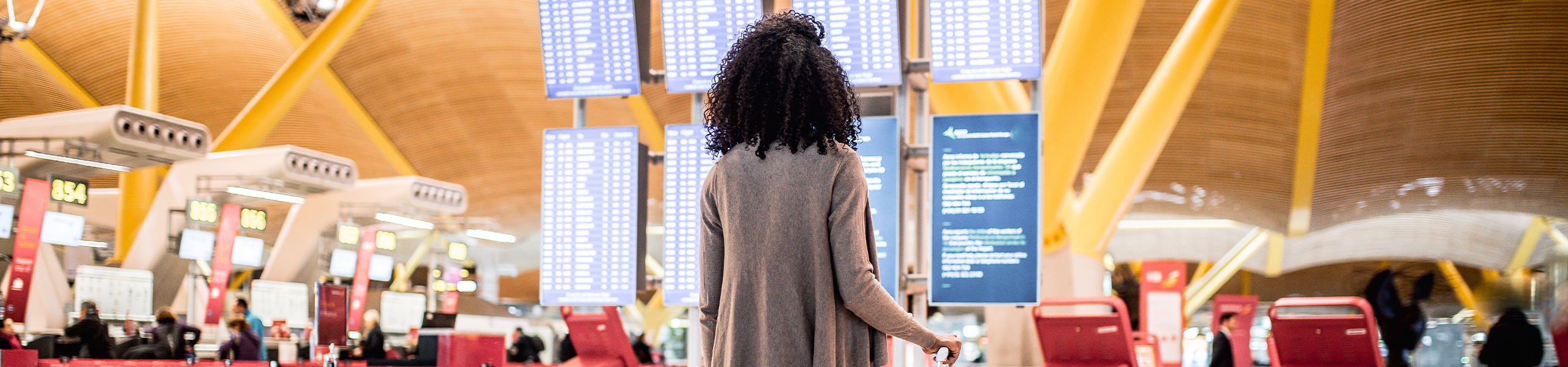 Woman looking at the timetable information panel in the airport with a suitcase