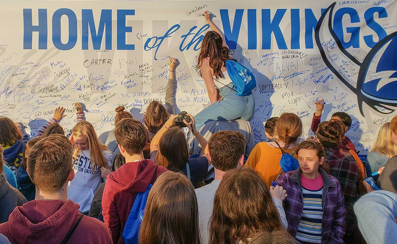 Students signing Home of the Vikings banner at the Paint B'ham Blue for WWU event